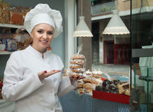 Portrait of young chef at confectionery display with pastry. Portrait of beautiful young chef at confectionery display with pastry stock images