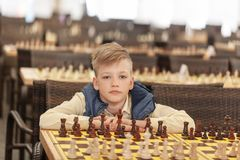 Portrait Young child on a chess tournament at a school.  stock photo