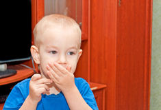 Portrait of a young. Child closing mouth with his hand Royalty Free Stock Images