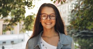 Portrait of the young child. Little girl in purple eyeglasses is smiling at camera in sun flares. 4k footage.