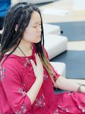 Portrait of young Chinese female with cute dreadlocks and thoughtful face sitting and meditating with eyes closed.  royalty free stock photography