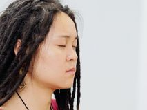 Portrait of young Chinese female with cute dreadlocks and thoughtful face sitting and meditating with eyes closed.  stock photo