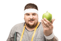 Portrait of young chubby man with measuring tape holding apple. Isolated on white stock photos