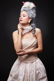 Portrait of a young cocky woman in a rococo style. Fluffy dress, crinoline, aristocratic pallor, vintage hairstyle stock photo