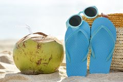 Young coconut, flipflops, and sunglasses on the sand. Portrait of young coconut, flipflops, and sunglasses on the sand for summer concept Stock Photo