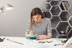 Portrait of young concentrated good-looking female freelance engineer with dark hair in striped clothes writing up tasks Royalty Free Stock Photos