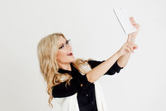 Portrait of young confident business lady, use tablet as the camera, white background Royalty Free Stock Images
