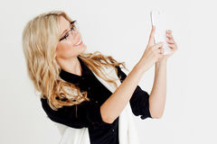 Portrait of young confident business lady, use tablet as the camera, white background Stock Photography