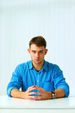 Portrait of a young confident businessman sitting at the table Royalty Free Stock Photography