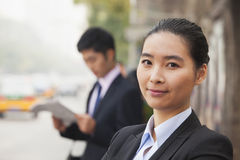 Portrait of young, confident businesswoman looking at the camera and smiling in the street, Beijing, China Royalty Free Stock Images