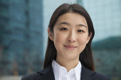 Portrait of young confident businesswoman outdoors among skyscrapers, close-up Stock Photo