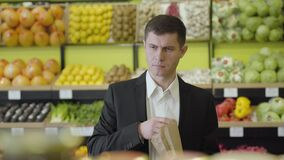 Portrait of young confident Caucasian man choosing eggplant in grocery and putting vegetable into pack. Handsome