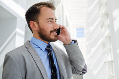 Portrait of a young confident intelligent man having cell telephone conversation during work break Stock Image