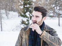 Handsome young man biting chocolate in snow. Portrait of young confident man biting chocolate bar on background of snows looking at camera royalty free stock images