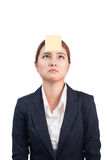 A portrait of a young confused business woman with a sticky note. On her forehead Royalty Free Stock Photo