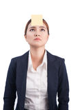 A portrait of a young confused business woman with a sticky note. On her forehead Royalty Free Stock Photography
