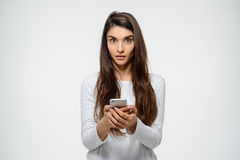 Portrait of young confused girl chatting over white background looking at camera Royalty Free Stock Images