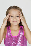 Portrait of young confused girl with hands on head against gray background Royalty Free Stock Photography