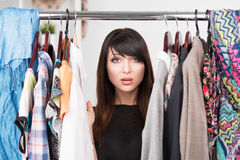 Portrait of young confused woman in front of a wardrobe Royalty Free Stock Photos