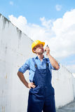 Construction Foreman Using Portable Radio. Portrait of young construction worker wearing hardhat using walkie-talkie giving instructions inside unfinished royalty free stock photography