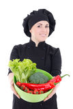 Portrait of young cook woman in black uniform with vegetables is Stock Images