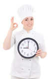 Portrait of young cook woman in uniform with clock showing ok si Stock Image