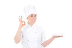 Portrait of young cook woman in uniform with empty plate showing Royalty Free Stock Photos