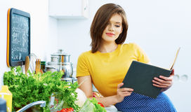 Portrait of young cooking woman in kitchen. Royalty Free Stock Images