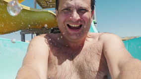Portrait of a young cool man, descends into the water slide in the water park, shoots himself on video. Slow Motion. Portrait of a young cool man, descends into stock footage
