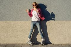Portrait of young cool smiling girl shod in rollerblades, holdin Stock Photography