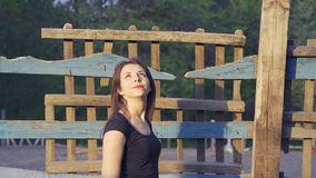 Portrait of a young country woman with dark brown hair and in a black T-shirt, shot in the countryside. Close-up. Sunset stock footage