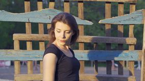 Portrait of a young country woman with dark brown hair and in a black T-shirt, shot in the countryside. Close-up. Sunset stock video