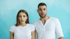 Portrait of young couple actively surprising and wondering looking into camera on blue background. Portrait of young couple actively surprising and excited Stock Image