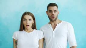 Portrait of young couple actively surprising and wondering looking into camera on blue background. Portrait of young couple actively surprising and excited Royalty Free Stock Images