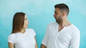 Portrait of young couple actively surprising and wondering looking each other. Indoors Stock Image