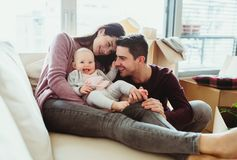 A portrait of young couple with a baby and cardboard boxes moving in a new home. A portrait of happy young couple with a baby and cardboard boxes, moving in a royalty free stock image
