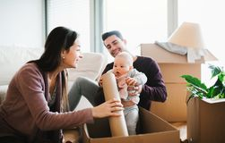 A portrait of young couple with a baby and cardboard boxes moving in a new home. A portrait of happy young couple sitting on a sofa with a baby and cardboard stock image