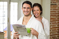 Portrait of young couple in bathrobe having tea and reading newspaper Royalty Free Stock Image