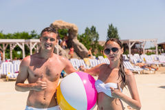 Portrait of Young Couple on Beach with Beach Ball Royalty Free Stock Photography