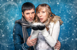 Portrait of young couple blowing snowflakes from hands Royalty Free Stock Photography