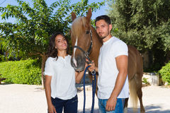 Portrait of young couple with a brown-blond horse Royalty Free Stock Image