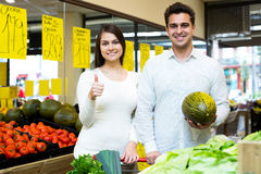 Portrait of young couple buying vegetables Stock Image