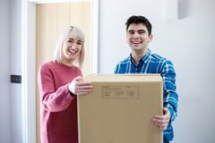 Portrait Of Young Couple Carrying Boxes Into New Home On Moving Day. Portrait Of Couple Carrying Boxes Into New Home On Moving Day royalty free stock photo