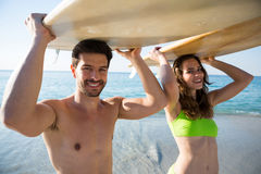 Portrait of young couple carrying surfboard at beach Royalty Free Stock Photo