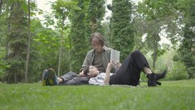Portrait young couple in casual clothes spending time together outdoors, having date. The guy sitting on the blanket on stock video