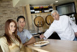 Portrait of a young couple with chef holding wine glass Stock Image