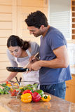 Portrait of a young couple cooking with a pan Royalty Free Stock Photo