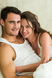 Portrait of young couple cuddling on bed Stock Photography