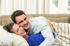 Portrait of young couple cuddling on sofa Stock Images