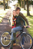 Portrait Of Young Couple With Cycle In Autumn Park Stock Image